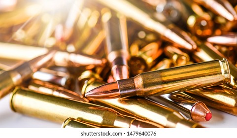 Pile of fire bullets or ammunition banner or panorama on dark stone table.  Hand guns weapon in background. Many projectiles into 9mm gun back light.