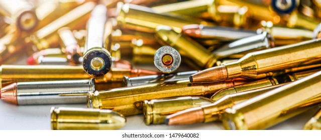 Pile of fire bullets or ammunition banner or panorama on dark stone table.  Hand guns weapon in background. Many projectiles into 9mm gun.