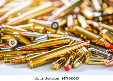 Pile of fire bullets or ammunition on dark stone table.  Hand guns weapon in background. Many projectiles into 9mm gun.