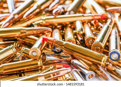 Pile of fire bullets or ammunition on whitetable. Many various projectiles into gun top view.