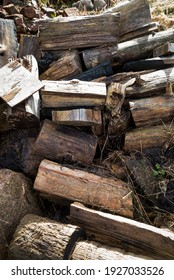 pile of firewood with old dried boards in a dry hall with an old castle stone wall in the background.
