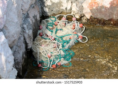 Pile of fishing nets held together with thick rope and small buoys left in corner of traditional stone wall at local harbour on warm sunny summer day