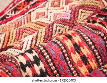 Pile of folded kilim rugs with shallow depth of field