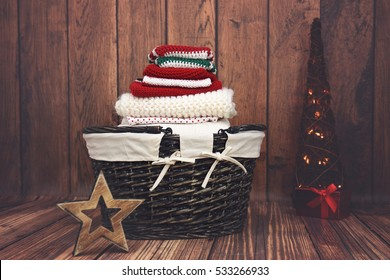 A pile of folded red, white and green knit Christmas clothes in a wicker basket with Christmas tree