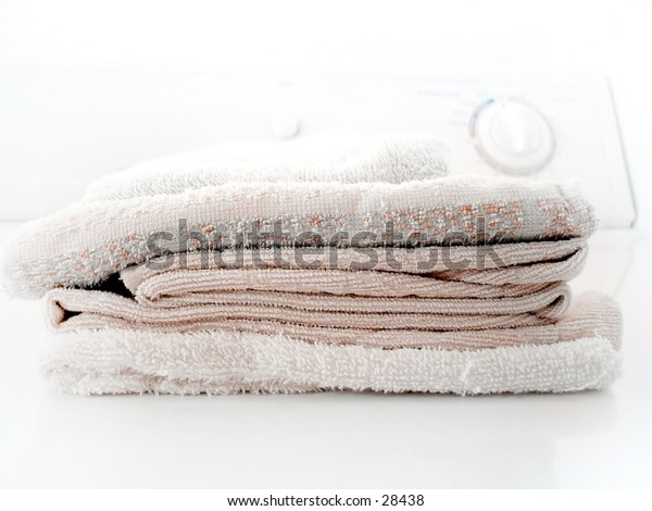 Pile of folded towels on a clothes dryer.