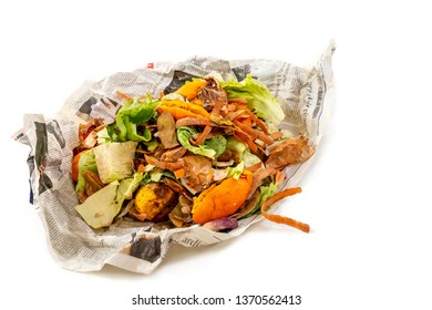 A pile of food waste, such as eggshells and fruit and vegetable peels, on a newspaper white background