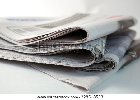 pile of four daily newspapers