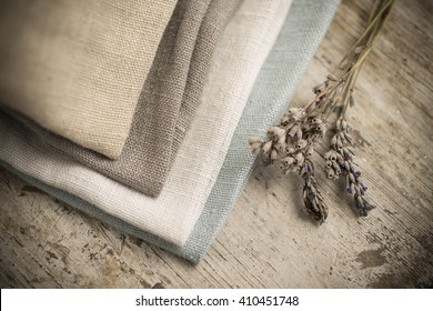 A pile of four folded dull-colored cotton fabric by a stalk of dried blossoms