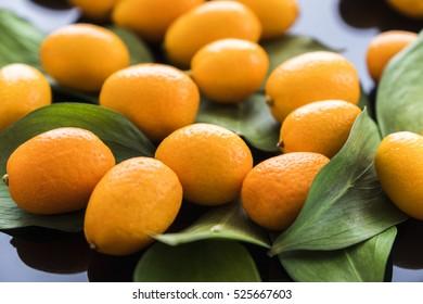 pile of fresh bright yellow kumquat on black glass desk with green leaves