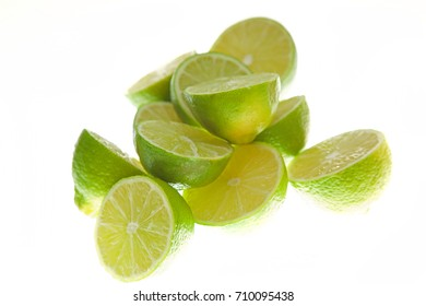 Pile of fresh cut limes on a white background