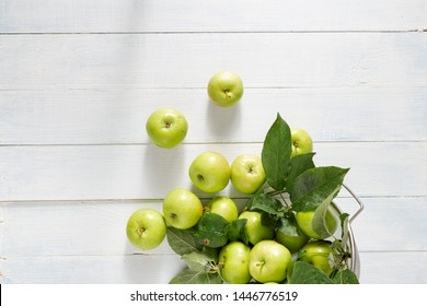 Pile of fresh green apple in colander on a wooden table top view