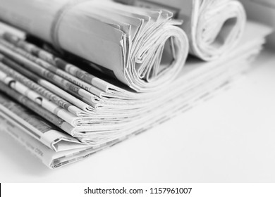 Pile of fresh morning newspapers on the table at office. Latest financial and business news in daily paper. Pages with information (headlines, articles, photos, text). Folded and rolled journals