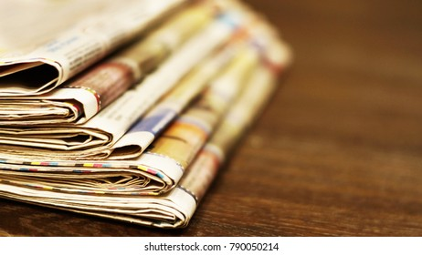 Pile of fresh morning newspapers on wooden table at the office. Business news  in daily papers. Folded and stacked yellow pages with selective focus. Blurred backgound texture