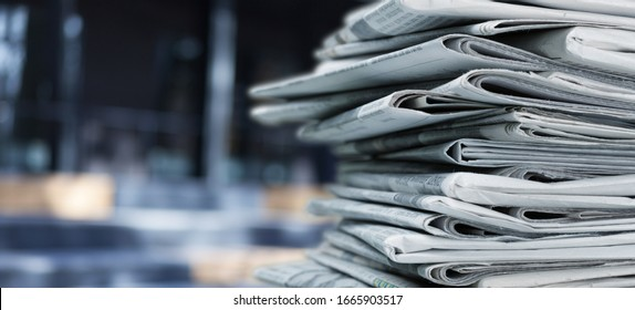 Pile of fresh newspapers on blur background