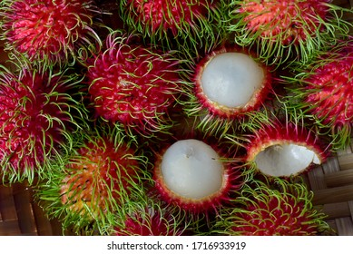 a pile of fresh rambutans on a wooden container. Hair fruits or rambutans is a tropical plant belonging to the lerak-tribe or Sapindaceae, originating from areas in Southeast Asia.
