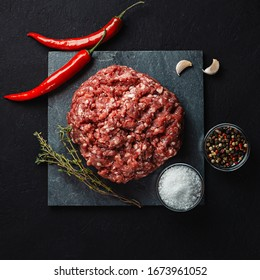 pile of fresh raw minced meat for meatballs with spices (pepper, salt) on a black background. Ingredient for the preparation of meat dishes