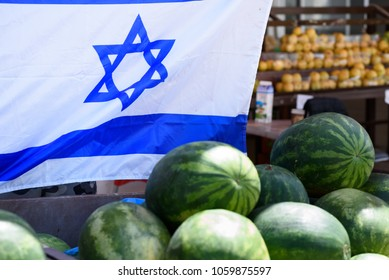 Pile of fresh ripe watermelons lying in big plastic box in fruit and vegetable Israeli supermarket  over Israel flag background.