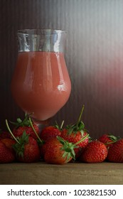 Pile of Fresh strawberries and juice in the glass cup on the wooden plank / Still Life image and select focus
