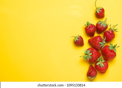 Pile of fresh strawberries on yellow background. Top view point.