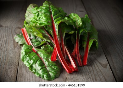 Pile of fresh swiss chard leaves on dark wooden table.
