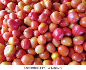 A pile of fresh tomatoes just arrived in the market.