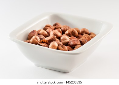 Pile of fried hazelnuts in a white ceramic bowl isolated on a white background.