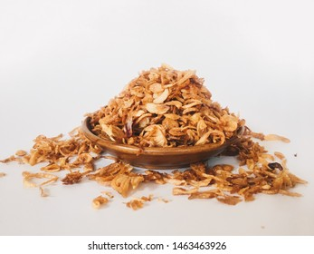 Pile of fried Indonesian Deep Onion fries (Bawang Goreng) or shallots with spread in several sides on wood plate isolated on white background.