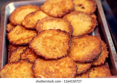 Pile of fried potato fritters at a fair.
