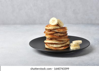 A pile of fritters on a black plate.  Pancakes are decorated with banana slices.  Light background.  Free space for text.