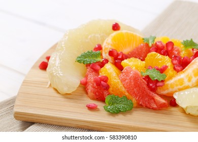 pile of fruit salad on wooden cutting board - close up