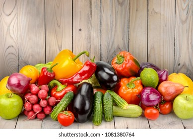 Pile fruits and vegetables on wooden table on background wooden wall. Copy space
