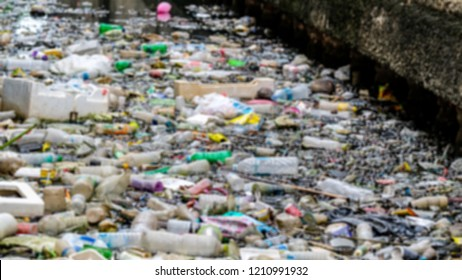 Pile of garbage form consumer products in canal are problems in big city, Blurry photo use for background.