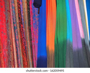 Pile of gentle folded shawls (scarfs) hanging at the market