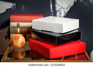 Pile of glossy carton gift boxes red black and white on nightstand next to burning candle