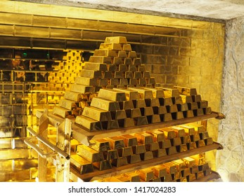 a pile of gold bars in front of a golden wall