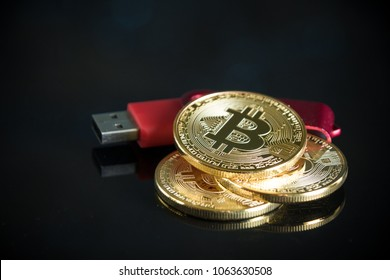 Pile of gold bitcoin cryptocurrency coins with red digital hardware wallet on dark background.