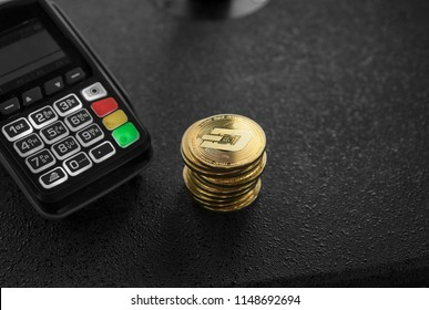 A pile of gold Dash Crypto currency coins and POS terminal. Dashes Cryptocurrency. E-commerce, business, finance concept, banking and payment.