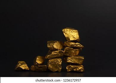 A pile of gold nuggets or gold ore on black background, precious stone or lump of golden stone, financial and business concept idea.