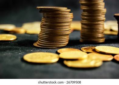 A pile of golden coins on dark background