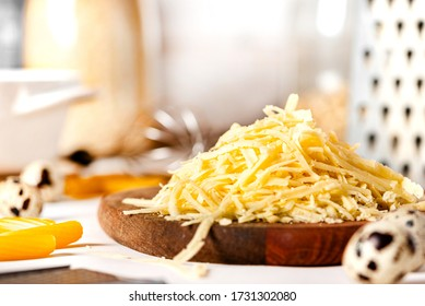 Pile of grated cheese on a cutting board close-up. Cooking pasta with grated cheese. Cheese and kitchen utensils on the table.