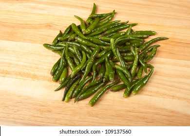A pile of green chilli peppers on a wooden board