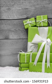 Pile of green Christmas presents, with snow on grey wooden background