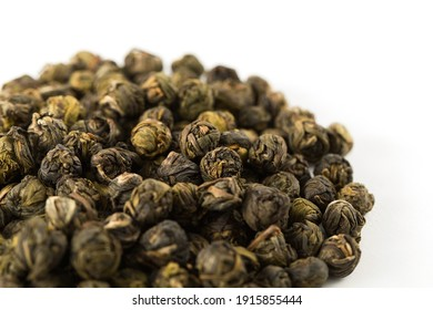 A pile of green jasmine pearl dried tea on a white background. Chinese traditional fragrant tea, rolled into small balls