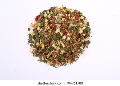 A pile of a green spice mix dried vegetables and herbs. Isolated on white background. Spices consist paprika garlic onion parsnip celery coriander oregano pepper rosemary