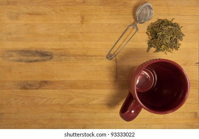 A pile of green tea sits with a strainer and cup of a counter top