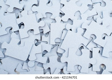 Pile of grey blank puzzle pieces background, closeup