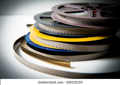 Pile of grey, blue, yellow and purple 8mm super8 movie reels on white background, vintage look and color effect