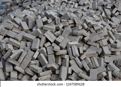Pile of grey cubes outdoor tiles. Chaotic stack of broken road tiles. Construction background. Mess geometric backdrop. Shades of grey pavement stone blocks.