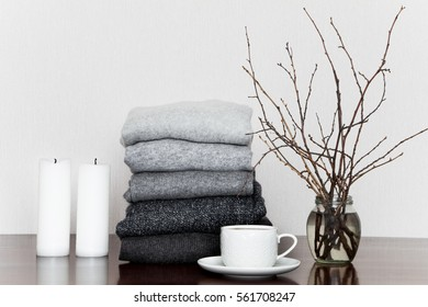 Pile of grey knitted sweaters on wooden table, decorated with candles, cup and a vase with branches. Winter clothes in all shades of grey, minimalism at home or in clothing store.