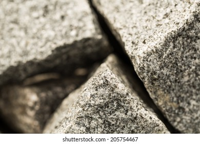 Pile of grunge granite stones near by the building, composition with low depth of field, selective focus.